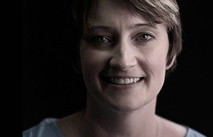 Woman smiling with dark background